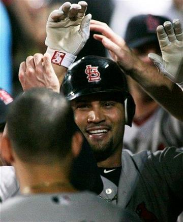 St. Louis Cardinals first baseman Albert Pujols (5) celebrates in the dugout with teammates after homering against the Atlanta Braves during the first inning of an MLB baseball game, Sunday Sept. 12, 2010, in Atlanta. (AP Photo/John Amis) By John Amis