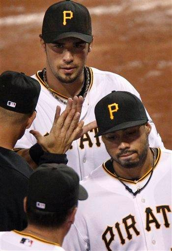 Pittsburgh Pirates' Garrett Jones, top, and Pedro Alvarez celebrate with teammates after the Pirates' 11-6 victory over the St. Louis Cardinals in a baseball game in Pittsburgh, Wednesday, Sept. 22, 2010. (AP Photo/Keith Srakocic) By Keith Srakocic