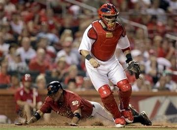 Houston Astros' Carlos Corporan, rear, scores as St. Louis Cardinals catcher Yadier Molina waits for the throw during the ninth inning of a baseball game on Wednesday, July 27, 2011, in St. Louis. (AP Photo/Jeff Roberson) By Jeff Roberson