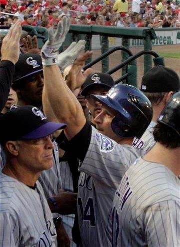 Colorado Rockies second baseman Mark Ellis (14) celebrates in the dugout after hitting a two-run home run in the first inning of a baseball game against the St. Louis Cardinals, Sunday, Aug. 14, 2011, in St. Louis.(AP Photo/Tom Gannam) By Tom Gannam