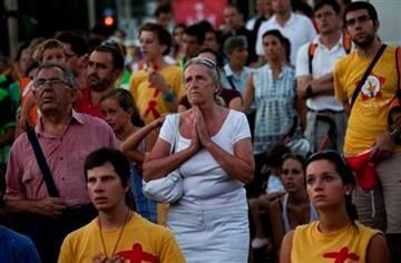 Pilgrims pray at the street during a mass at the Cibeles square, Tuesday Aug. 16, 2011, ahead to the visit of Pope Benedict XVI in Madrid next Aug. 18- 21. (AP Photo/Emilio Morenatti) By Emilio Morenatti