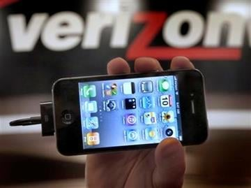 On the first day that the popular iPhone was available at Verizon stores, Chris Cioban, manager of the Verizon store in Beachwood, Ohio, holds up an iPhone on Thursday, Feb. 10, 2011. (AP Photo/Amy Sancetta) By Amy Sancetta