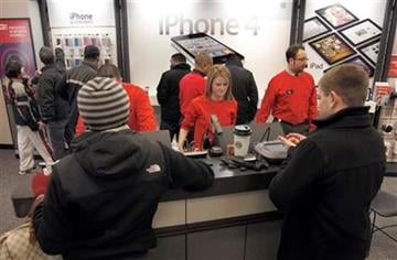 People flock to the cashier and the iPhone display on the first day that the popular iPhone was available at Verizon stores, at the Verizon Wireless store in Beachwood, Ohio on Thursday, Feb. 10, 2011. (AP Photo/Amy Sancetta) By Amy Sancetta
