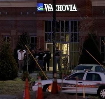 A hostage is led from a Wachovia Bank in Cary, N.C., where an armed man took four people hostage Thursday, Feb. 10, 2011. Television footage shows the subject was shot as he exited the bank with a hostage. (AP Photo/Gerry Broome) By Gerry Broome
