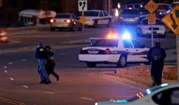 Police run with a hostage at a Wachovia Bank in Cary, N.C., where an armed man took four people hostage Thursday, Feb. 10, 2011. Television footage shows the subject was shot as he exited the bank with a hostage. (AP Photo/Gerry Broome) By Gerry Broome