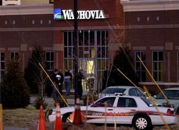 Police enter a Wachovia Bank in Cary, N.C., where an armed man took four people hostage Thursday, Feb. 10, 2011. Television footage shows the subject was shot as he exited the bank with a hostage. (AP Photo/Gerry Broome) By Gerry Broome