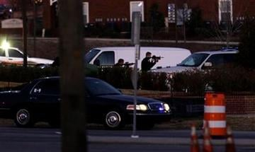 Police take aim at a suspect at a Wachovia Bank in Cary, N.C., where an armed man took four people hostage Thursday, Feb. 10, 2011. Television footage shows the subject was shot as he exited the bank with a hostage. (AP Photo/Gerry Broome) By Gerry Broome