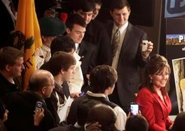 A rapt crowd takes cell phone pictures as a Sarah Palin impersonator Patti Lyons, right, does an interview at the Conservative Political Action Conference in Washington, on Friday, Feb. 11, 2011. (AP Photo/Jacquelyn Martin) By Jacquelyn Martin