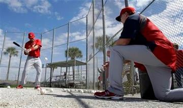 St. Louis Cardinals batting coach Mark McGwire, right, tosses a ball for Cardinals catcher Yadier Molina, left, to hit into a net during spring training baseball Monday, Feb. 14, 2011, in Jupiter, Fla. (AP Photo/Jeff Roberson) By Jeff Roberson