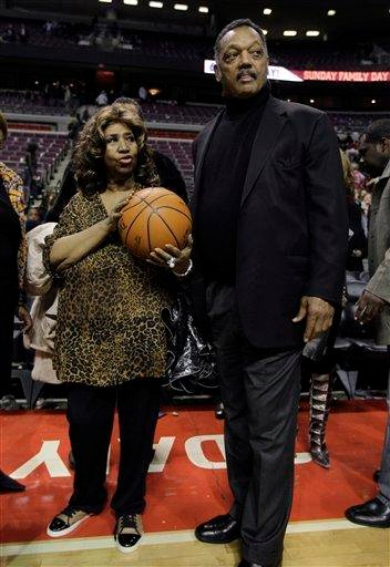 Aretha Franklin walks on the court with Jesse Jackson after the Detroit Pistons-Miami Heat NBA basketball game in Auburn Hills, Mich., Friday, Feb. 11, 2011. (AP Photo/Paul Sancya) By Paul Sancya