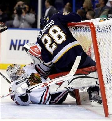 St. Louis Blues' Carlo Colaiacovo (28) gets tangled up with Chicago Blackhawks goalie Corey Crawford in the second period of an NHL hockey game Monday, Feb. 21, 2011, in St. Louis. (AP Photo/Tom Gannam) By Tom Gannam