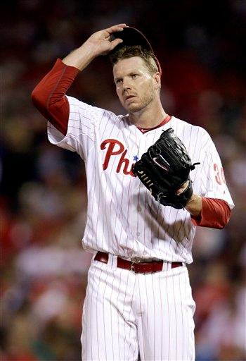 Philadelphia Phillies starting pitcher Roy Halladay adjusts his hat after walking St. Louis Cardinals' Nick Punto in the third inning of a baseball game, Monday, Sept. 19, 2011, in Philadelphia. (AP Photo/Matt Slocum) By Matt Slocum