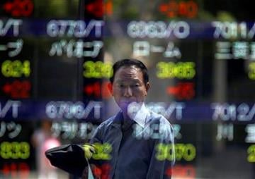 A man is reflected on an electronic stock board of a securities firm in Tokyo, Japan, Friday, Sept. 16, 2011. The benchmark Nikkei 225 stock average rose 150.83 points, to end morning session at 8,819.69.(AP Photo/Itsuo Inouye) By Itsuo Inouye