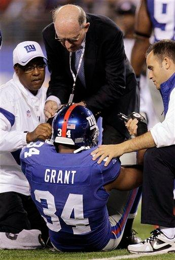 New York Giants defensive back Deon Grant is helped up by trainers during the first quarter of an NFL football game against the St. Louis Rams on Monday, Sept. 19, 2011, in East Rutherford, N.J. (AP Photo/Julio Cortez) By Julio Cortez