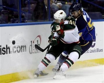 Minnesota Wild's Jared Spurgeon (46) battles St. Louis Blues' Anthony Nigro (54) for the loose puck in the second period of a preseason NHL hockey game on Thursday, Sept. 22, 2011, in St. Louis. (AP Photo/Tom Gannam) By Tom Gannam