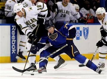 Dallas Stars' Eric Godard, left, and St. Louis Blues' T.J. Oshie, right, chase a loose puck during the first period of an NHL hockey game Saturday, Oct. 1, 2011, in St. Louis. (AP Photo/Jeff Roberson) By Jeff Roberson