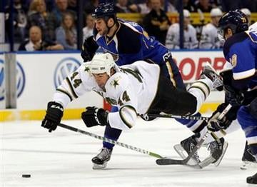 Dallas Stars' Sheldon Souray (44) and St. Louis Blues' Anthony Peluso, top, chase a loose puck during the first period of an NHL hockey game Saturday, Oct. 1, 2011, in St. Louis. (AP Photo/Jeff Roberson) By Jeff Roberson