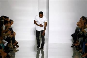 Rap singer Kanye West acknowledges applause at the end of his spring-summer 2012 ready-to-wear collection presented Saturday, Oct.1, 2011 in Paris. (AP Photo/Francois Mori) By Francois Mori