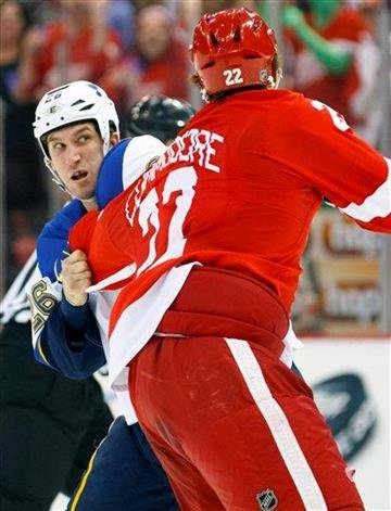 Detroit Red Wings defenseman Mike Commodore (22) and St. Louis Blues right wing B.J. Crombeen (26) fight in the second period of an NHL hockey game in Detroit, Saturday, Dec. 31, 2011. (AP Photo/Rick Osentoski) By Rick Osentoski