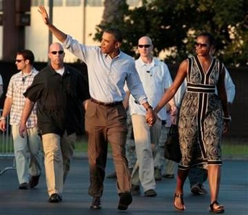 President Barack Obama and first lady Michelle Obama walks across the tarmac to board Air Force One at Hickam Air Force Base in Monday, Jan. 2, 2012, in Honolulu, en route to Washington after a family vacation. (AP Photo/Carolyn Kaster) By Carolyn Kaster