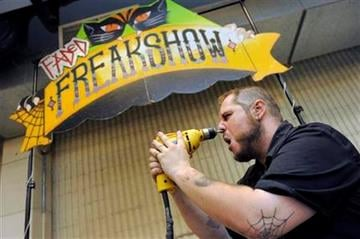 Aaron Woody, 29, of Fort Collins, drills a masonry bit into his face at the freak show at the first Denver County Fair in Denver on Thursday, July 28, 2011. (AP Photo/Chris Schneider) By Chris Schneider
