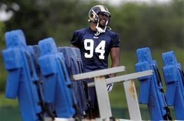 St. Louis Rams first-round draft pick Robert Quinn smiles as he works near a tackling sled during NFL football training camp Sunday, July 31, 2011, in St. Louis. (AP Photo/Jeff Roberson) By Jeff Roberson