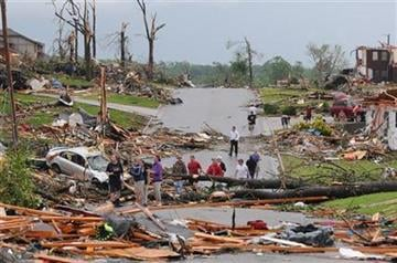 Residents of Joplin, Mo, survey the damage after a tornado hit the city on Sunday, May 22, 2011. The tornado tore a path a mile wide and four miles long destroying homes and businesses. (AP Photo/Mike Gullett) By Mike Gullett