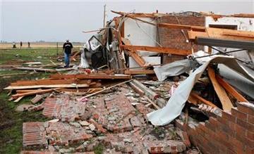 Matt McElvany camina sobre casa de un amigo suyo que fue derribada por un tornado en Piedmont, Oklahoma, el martes 24 de mayo de 2011. (AP Foto/Sue Ogrocki) By Sue Ogrocki