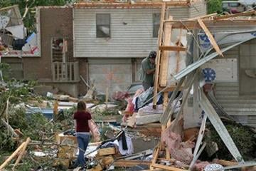 People make their way through the wreckage of a home damaged by a tornado in Sedalia, Mo., on Wednesday, May 25, 2011. (AP Photo/Dan Gill) By Dan Gill
