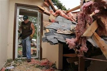 Darren Lazanby, Sedalia, Mo, helps carry belongings out of a house damaged by the tornado in Sedalia, Mo., on Wednesday May 25, 2011. (AP Photo/Dan Gill) By Dan Gill
