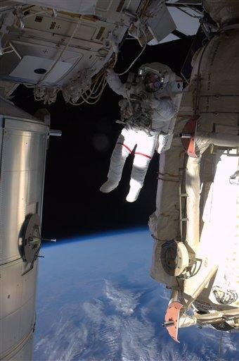 This image provided by NASA shows astronaut Andrew Feustel hanging by one arm from the International Space Station backdropped by the blue earth during the third spacewalk Wednesday May 25, 2011. (AP Photo/NASA) By Ron Garan