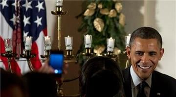 President Barack Obama greets people as he stands next to a lit Menorah during the Hanukkah reception in the Grand Foyer of the White House, Thursday, Dec. 13, 2012, in Washington. (AP Photo/Carolyn Kaster) By Carolyn Kaster
