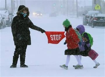 A crossing guard stops traffic as children walk to school in cold and snowy weather as Illinois receives its first significant snowfall in nearly 11 months Thursday, Jan. 12, 2012 in Springfield, Ill. (AP Photo/Seth Perlman) By Seth Perlman