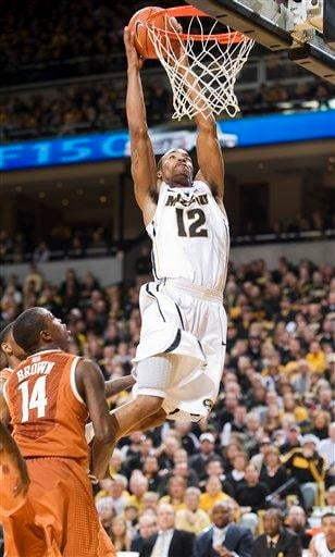 Missouri's Marcus Denmon, right, dunks the ball over Texas' J'Covan Brown, left, during the second half of an NCAA college basketball game Saturday, Jan. 14, 2012, in Columbia, Mo. Missouri won the game 84-73. (AP Photo/L.G. Patterson) By L.G. PATTERSON