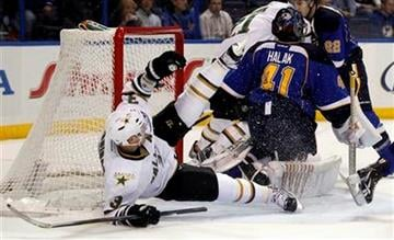 Dallas Stars' Stephane Robidas (3) falls near the net as St. Louis Blues goalie Jaroslav Halak, of Slovakia, defends during the first period of an NHL hockey game Monday, Jan. 16, 2012, in St. Louis. (AP Photo/Jeff Roberson) By Jeff Roberson