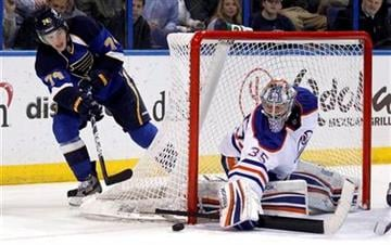 St. Louis Blues' T.J. Oshie, left, makes a pass around Edmonton Oilers goalie Nikolai Khabibulin, of Russia, during the second period of an NHL hockey game Thursday, Jan. 19, 2012, in St. Louis. (AP Photo/Jeff Roberson) By Jeff Roberson