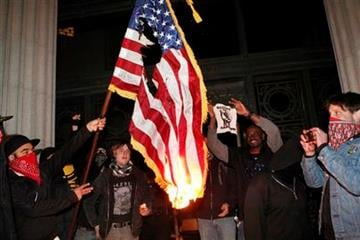 Occupy Oakland protestors burn an American flag found inside Oakland City Hall during an Occupy Oakland protest on the steps of City Hall, Saturday, January 28, 2012, in Oakland, Calif.  (AP Photo/Beck Diefenbach) By Beck Diefenbach
