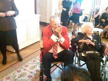 Stan Musial plays his harmonica with his wife, Lil, at his side. By KMOV Web Producer