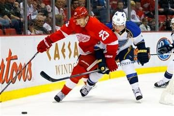 Detroit Red Wings defenseman Brad Stuart (23) and St. Louis Blues right wing Jamie Langenbrunner (15) battle for the puck in the first period of an NHL hockey game in Detroit, Saturday, Dec. 31, 2011. (AP Photo/Rick Osentoski) By Rick Osentoski
