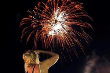 A woman photographs a fireworks show over the Delaware River for the Fourth of July holiday Saturday, July  2, 2011, in Trenton, N.J. (AP Photo/Mel Evans) By Mel Evans