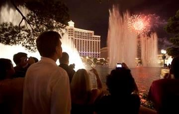 Tourists watch Independence Day weekend fireworks explode over Caesar's Palace as the Bellagio fountain show plays simultaneously, Sunday, July 3, 2011, in Las Vegas. (AP Photo/Julie Jacobson) By Julie Jacobson