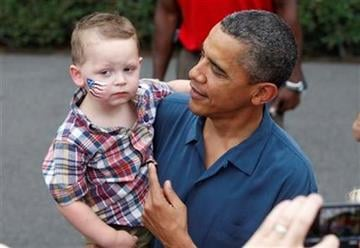 President Barack Obama picks up a child as he greets military families at an Independence Day celebration on the South Lawn of the White House in Washington, Monday, July 4, 2011. (AP Photo/Charles Dharapak) By Charles Dharapak