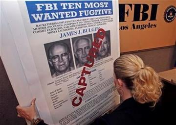 FBI Special Agent Mary Prang sets up a 'wanted' poster overstamped 'captured' for James 'Whitey' Bulger, before a news conference at FBI headquarters in Los Angeles Thursday, June 23, 2011. (AP Photo/Reed Saxon) By Reed Saxon