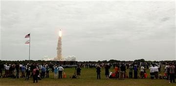 Una multitud observa a distancia el despegue del transbordador Atlantis del Centro Espacial Kennedy, en Cabo Ca?averal, Florida, el viernes 8 de julio de 2011. (AP foto/Morry Gash) By Morry Gash