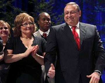 Gov. Paul LePage, with his wife, Ann LePage, at left, gives a thumbs-up while being introduced as Maine's next governor during his inauguration on Wednesday, Jan. 5, 2011, in Augusta, Maine.  (AP Photo/Pat Wellenbach) By Pat Wellenbach