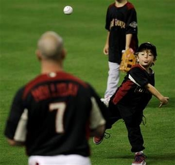 National League's Matt Holliday of the St. Louis Cardinals watches as his son Ethan throws a ball to him before batting practice for the MLB All-Star baseball game Monday, July 11, 2011, in Phoenix. (AP Photo/David J. Phillip) By David J. Phillip