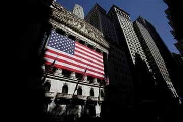 In this June 2, 2011 photo, American flags are displayed on the New York Stock Exchange in New York. Global stocks took another pounding Tuesday, July 12, 2011.  (AP Photo/Seth Wenig) By Seth Wenig