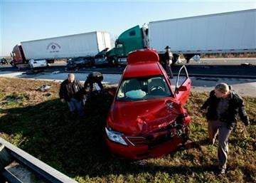 Funcionarios junto a veh?culos accidentados en la autopista interestatal 75 a la altura de Paynes Prairie, el domingo 29 de enero de 2012, al sur de Gainesville, Florida. (Foto AP/Matt Stamey, The Gainesville Sun) By Matt Stamey