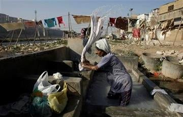 A Pakistani man washes clothes at a local washing pool in Karachi, Pakistan on Thursday, Feb. 2, 2012. (AP Photo/Fareed Khan) By Fareed Khan