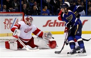 Detroit Red Wings goalie Jimmy Howard, left, deflects a puck as St. Louis Blues' Alexander Steen, right, looks on during the second period of an NHL hockey game, Tuesday, Dec. 6, 2011, in St. Louis. (AP Photo/Jeff Roberson) By Jeff Roberson